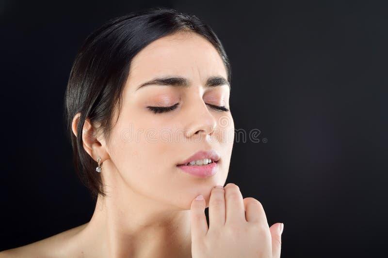 Ładna kobieta delikatnie przekręca ona wokoło jej podbródka z ona palce oczy zamykający, obracający jej głowę w kierunku pracowni zdjęcia stock