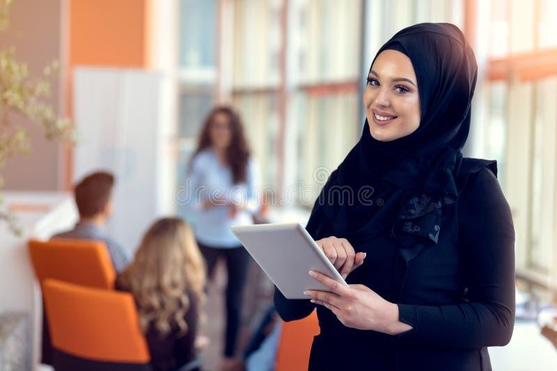 Ładna kobieta jest ubranym hijab przed laptop rewizją i robi biurowej pracie, biznesowi, finanse i staci roboczej pojęciu, fotografia royalty free