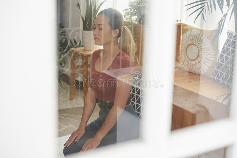 Ładna kobieta medytuje w domu obrazy royalty free