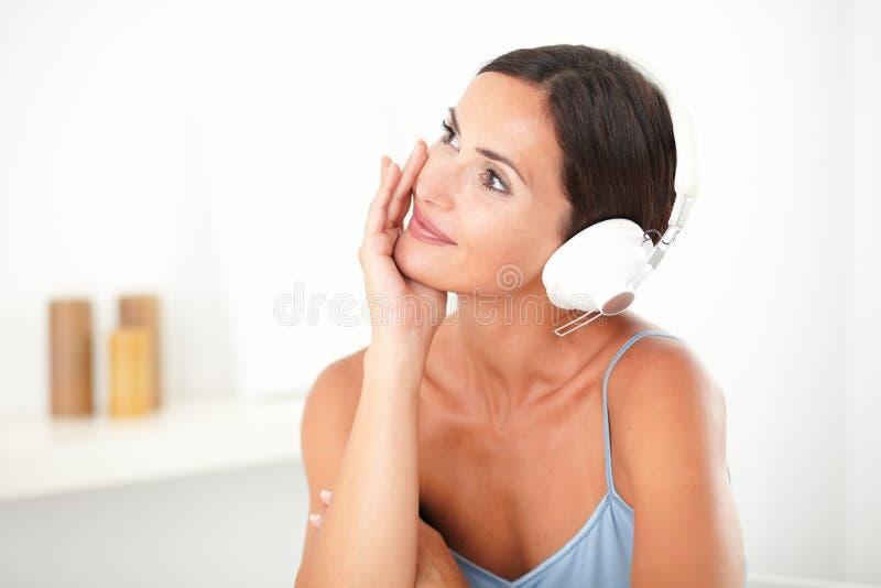 Ładna kobieta ono uśmiecha się podczas gdy słuchający muzyka obraz royalty free