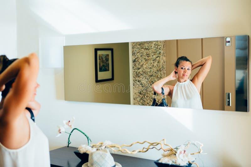 Ładna kobieta podziwia przed lustrem zdjęcia stock