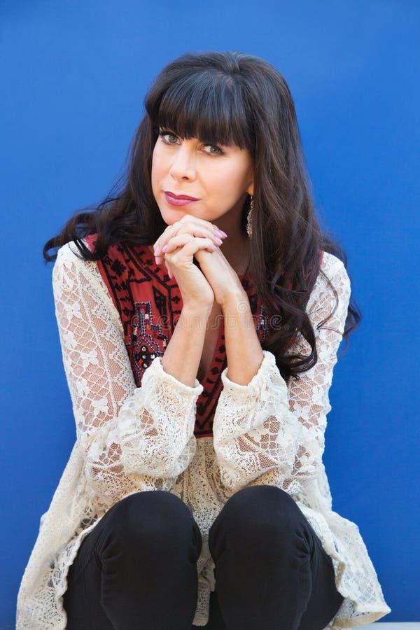Ładna kobieta przed błękit ścianą fotografia stock