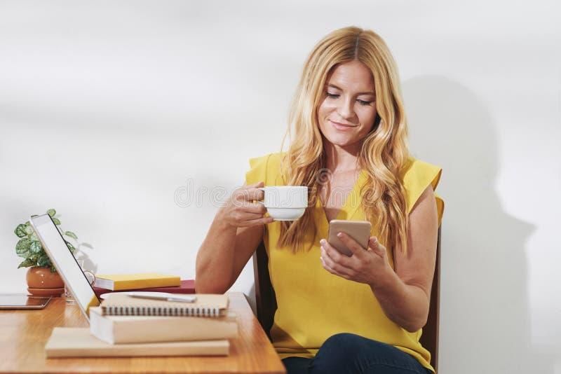 Ładna kobieta sprawdza wiadomości tekstowe obrazy stock