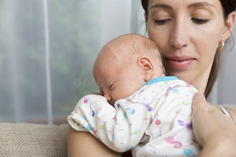 Ładna kobieta trzyma nowonarodzonego dziecka w ona ręki zdjęcia royalty free