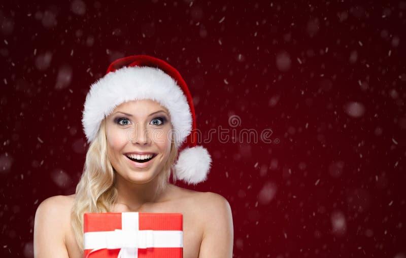 Ładna kobieta w Bożych Narodzeń nakrętki rękach teraźniejszych fotografia stock
