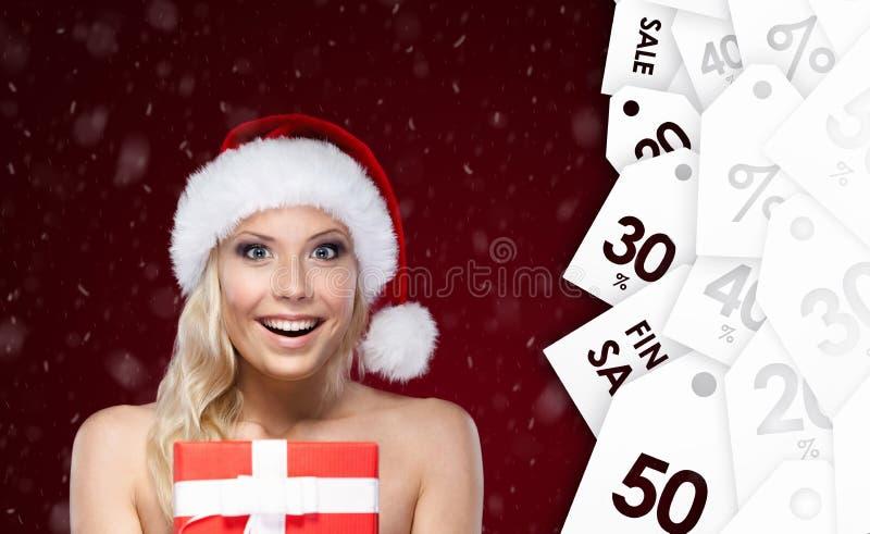 Ładna kobieta w Bożych Narodzeń nakrętki rękach teraźniejszych obraz royalty free