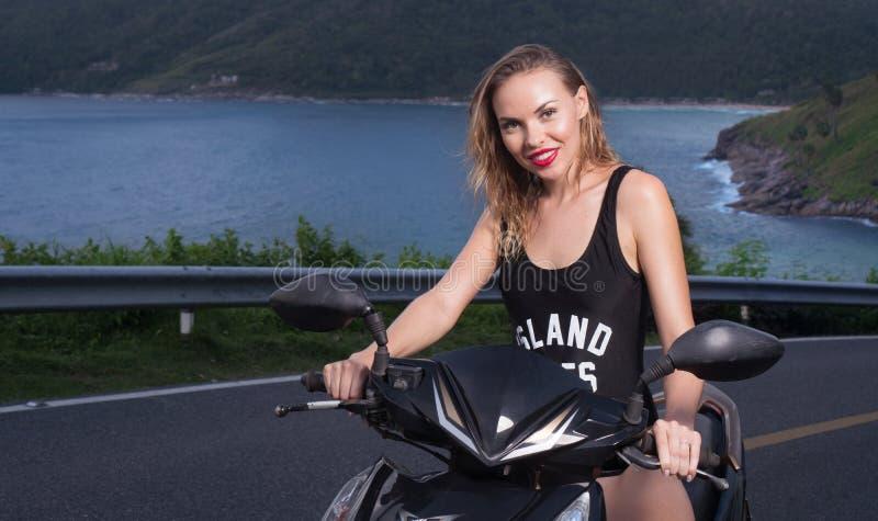 Ładna kobieta w czarnym swimwear na motorowej hulajnoga zdjęcia stock
