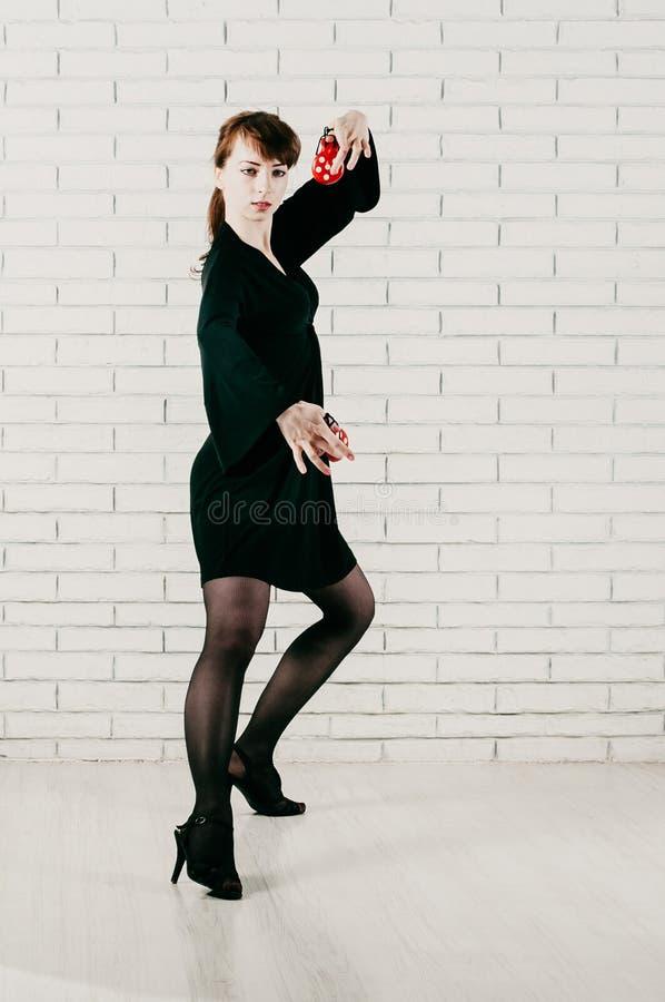 Ładna kobieta w czerni sukni, tanczy z czerwonymi kastanietami, białymi obraz stock