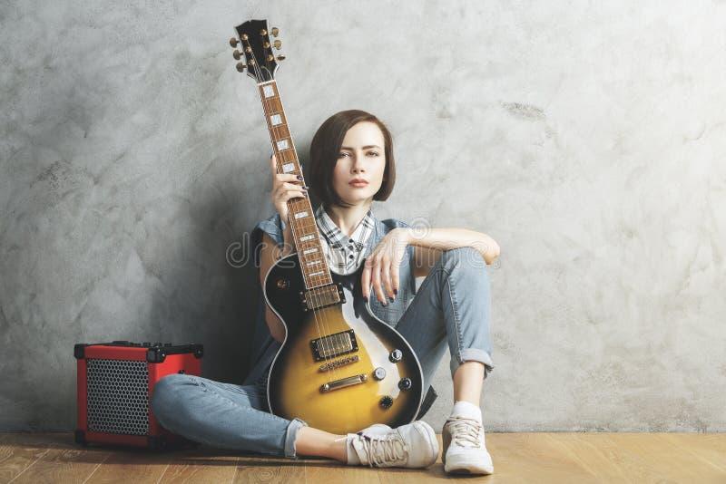 Ładna kobieta z gitarą w studiu fotografia stock