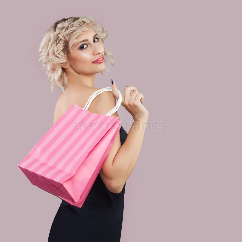 Ładna kobieta z torbą na zakupy na różowym tle obraz royalty free