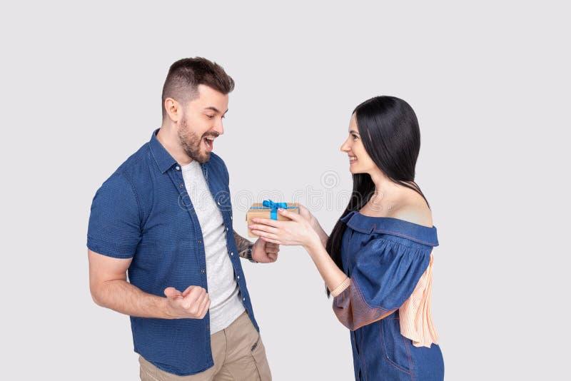 Ładna kobieta zaskakuje jej chłopaka z prezentem odizolowywał być ubranym drelichową odzież na szarości tle zdjęcie royalty free