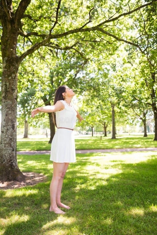 Ładna kobiety pozycja na trawie w parku obraz royalty free