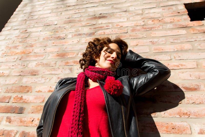 Ładna kobiety pozycja przy ściana z cegieł zdjęcie royalty free