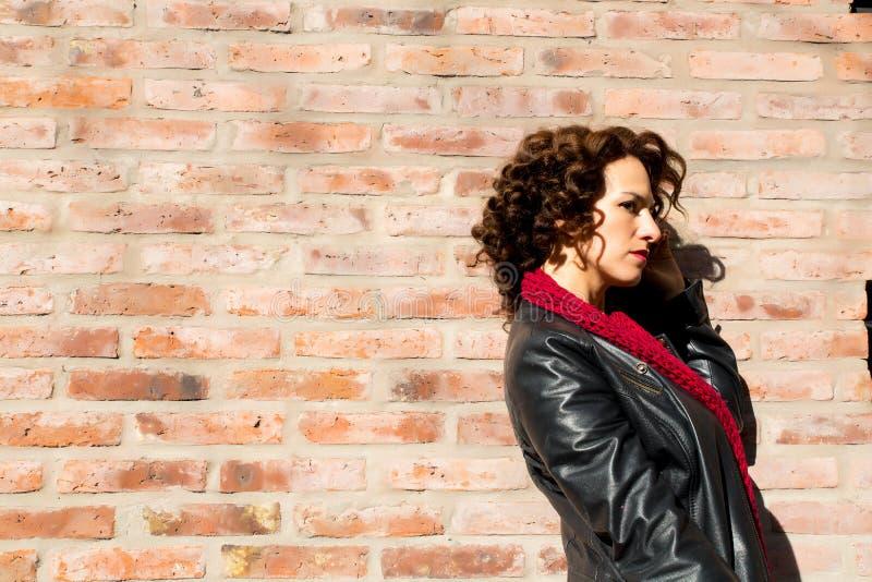 Ładna kobiety pozycja przy ściana z cegieł zdjęcia royalty free