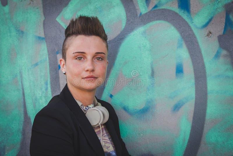 Ładna krótkiego włosy dziewczyna pozuje przeciw ścianie zdjęcie stock