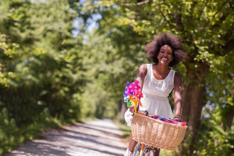 Ładna młoda amerykanin afrykańskiego pochodzenia kobieta jedzie rower w lesie fotografia royalty free