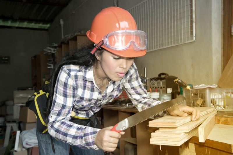 Ładna młoda Azjatycka kobieta używa rękę zobaczył ciąć niektóre drewno fotografia stock