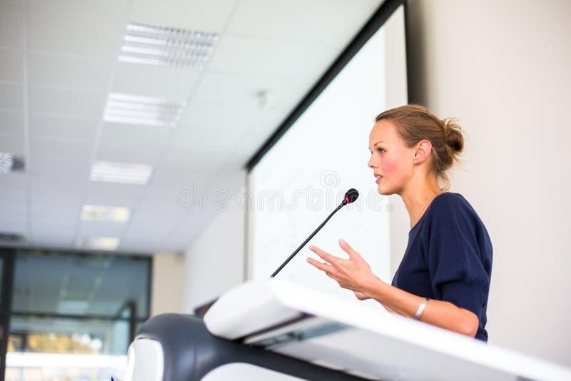 Ładna, młoda biznesowa kobieta daje prezentaci, zdjęcie royalty free