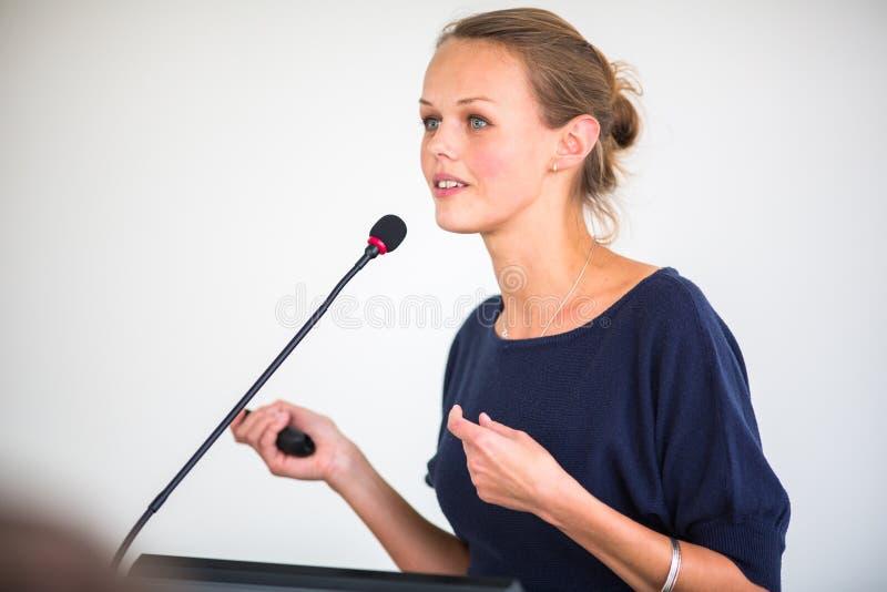 Ładna, młoda biznesowa kobieta daje prezentaci, obraz stock
