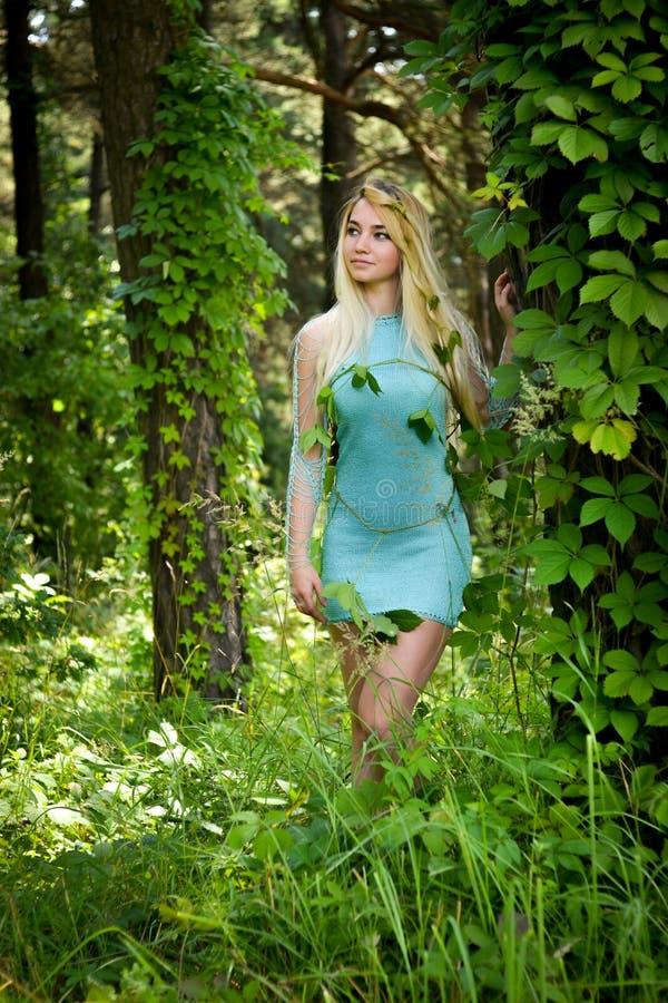 Ładna młoda blondynki dziewczyna z długie włosy w turkus sukni pozyci w zielonym lesie obraz stock