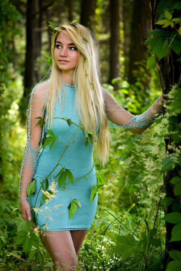 Ładna młoda blondynki dziewczyna z długie włosy w turkus sukni pozyci w zielonym lesie obrazy stock