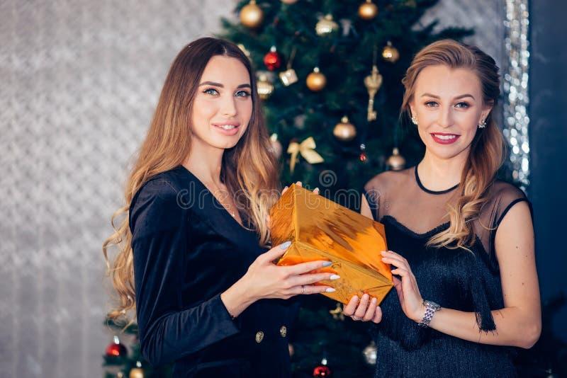 Ładna młoda blondynki kobieta daje atrakcyjnemu młodemu przyjacielowi niespodzianka prezentowi blisko choinki zdjęcie stock