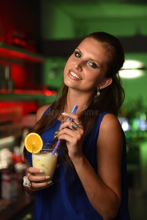Ładna młoda brunetki kobieta pije koktajl w barze fotografia stock