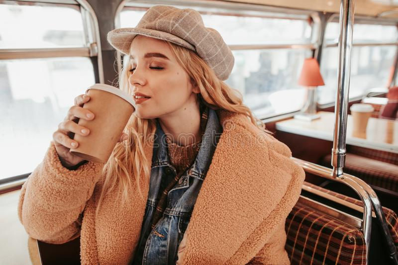 Ładna młoda dama pije kawę w autobusowej kawiarni obrazy stock