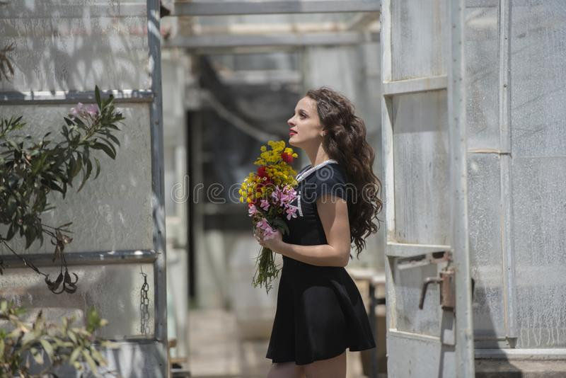 Ładna młoda dama trzyma bukiet kwiaty zdjęcie royalty free