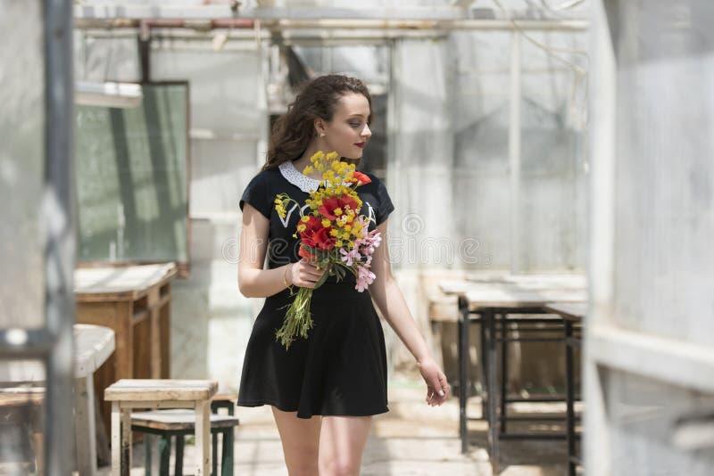 Ładna młoda dama trzyma bukiet kwiaty obraz stock