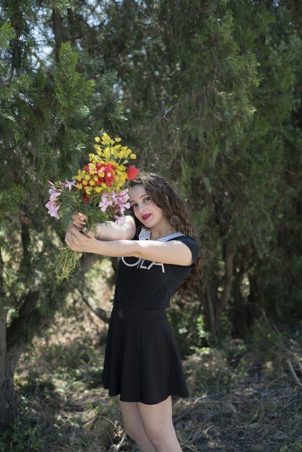 Ładna młoda dama trzyma bukiet kwiaty zdjęcia stock