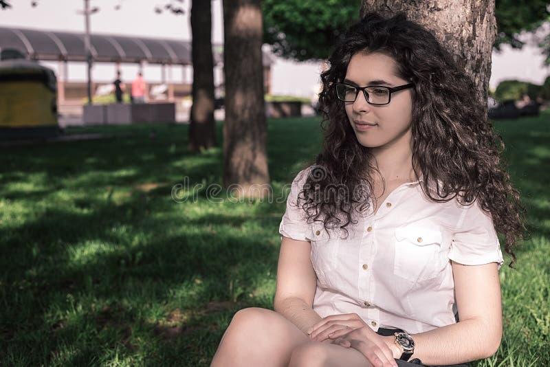 Ładna młoda dziewczyna jest usytuowanym na ziemi w parku w białej bluzce i czerni spódnica i dostajemy spoczynkowymi zdjęcie stock