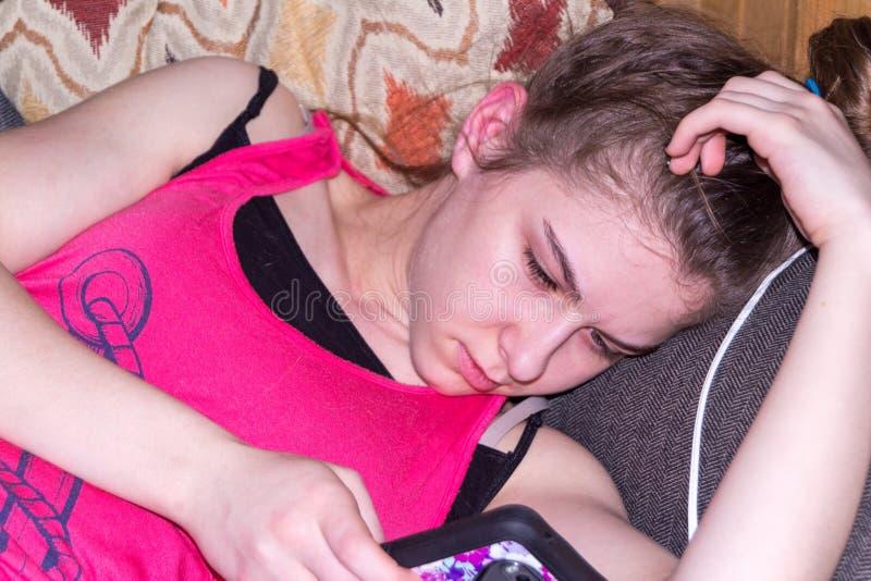 Ładna młoda dziewczyna kłaść na leżance bawić się z telefonem i relaksować obraz stock