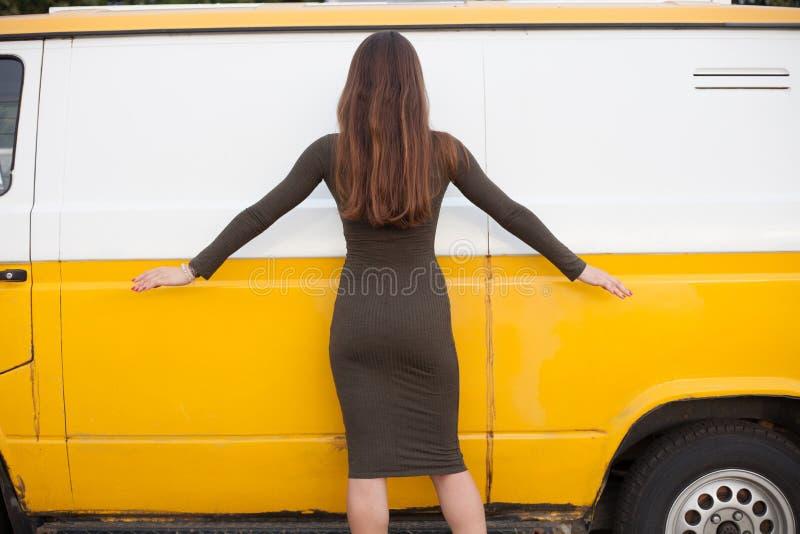 Ładna młoda dziewczyna pozuje blisko żółtego autobusu w krótkiej seksownej sukni kurczątko seksowny Tylni widok od plecy zdjęcia royalty free