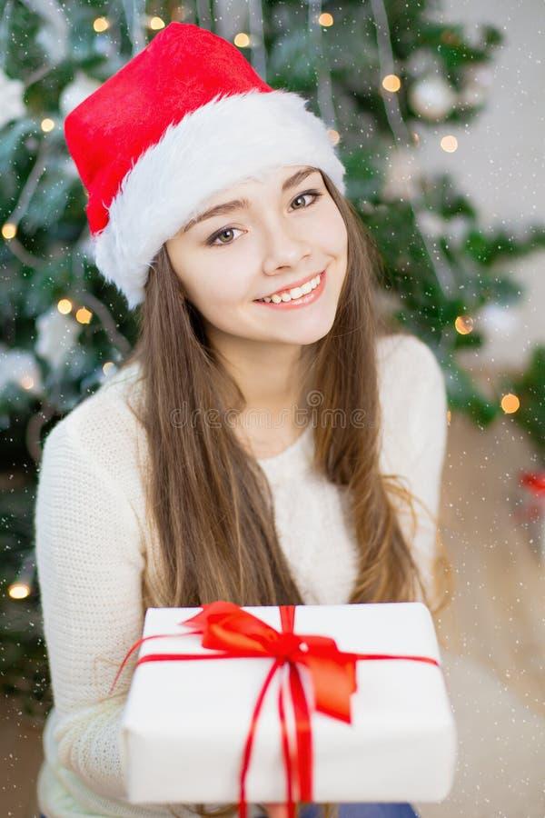 Ładna młoda dziewczyna w Santa Claus kapeluszowy uśmiechać się teraźniejszej pobliskiej choinki i trzymać Tło Bokeh zdjęcie stock