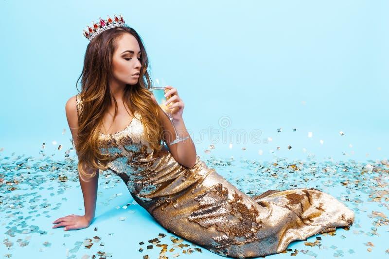 Ładna młoda dziewczyna w złotej sukni z szampanem obrazy royalty free