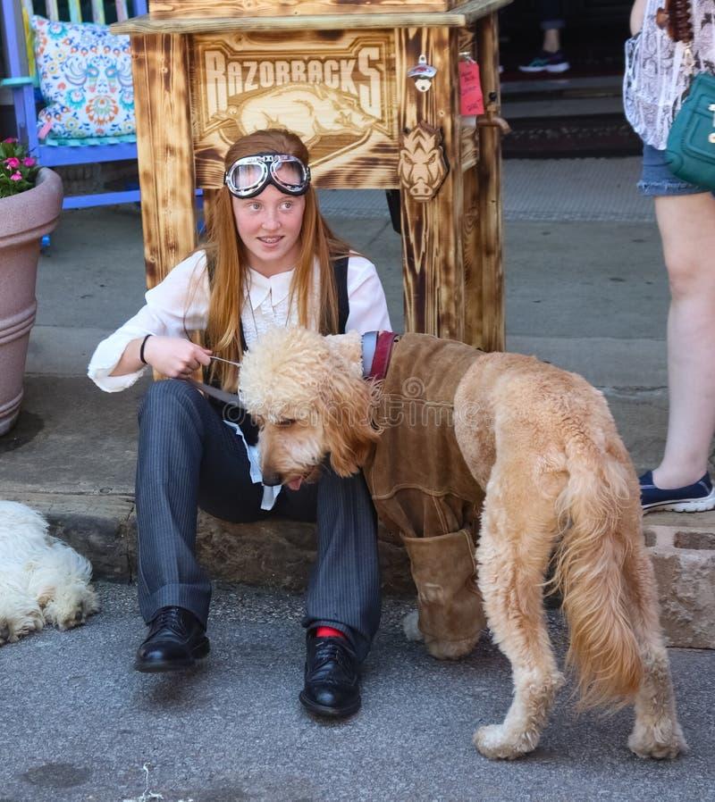 Ładna młoda dziewczyna z brasami i długim czerwonym włosy z steampunk gogle siedzi na krawężniku z labradoodle psem ubierającym w obraz royalty free