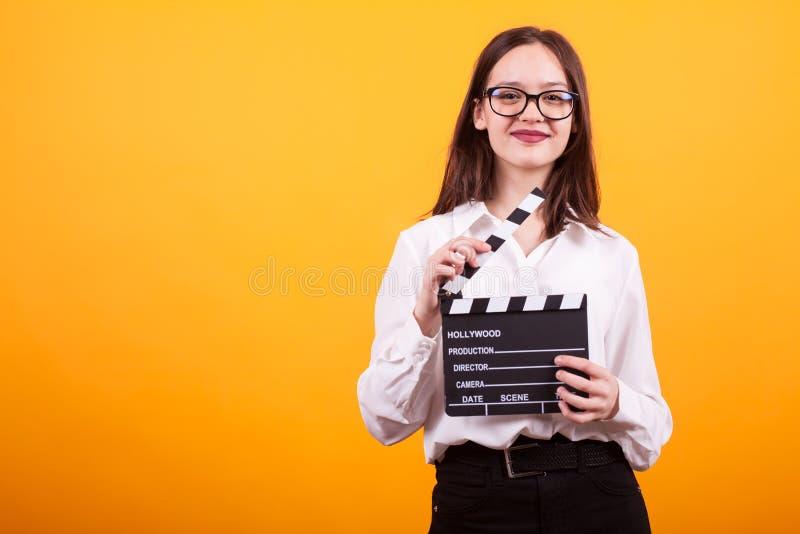 Ładna młoda dziewczyna z kino deską trzyma mnie w ona i ono uśmiecha się kamera w studiu nad żółtym tłem ręki zdjęcia stock