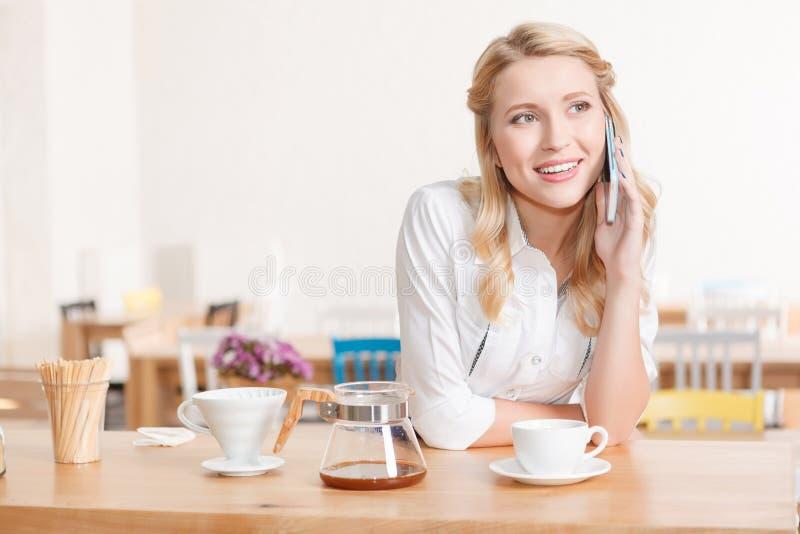 Ładna młoda kelnerka opowiada na telefon komórkowego zdjęcia stock