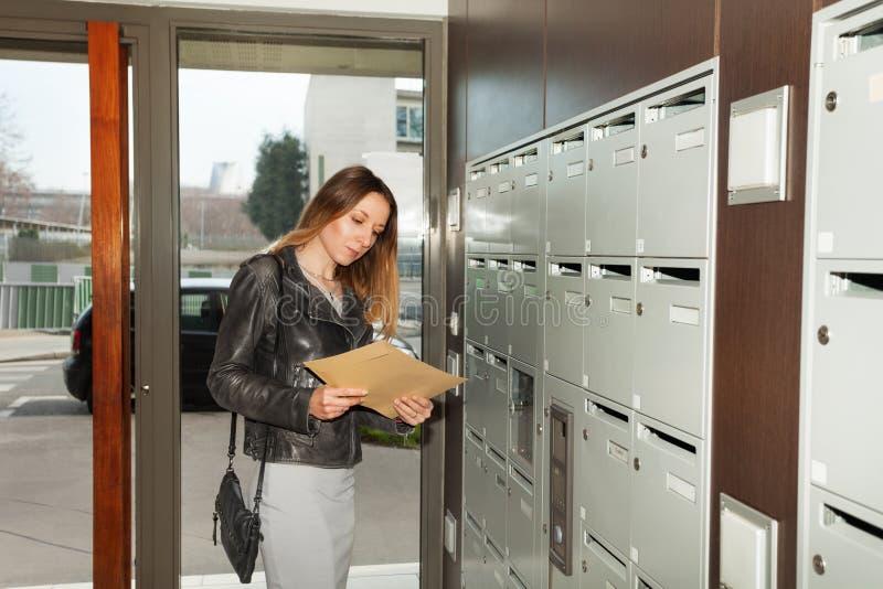 Ładna młoda kobieta bierze kopertę od skrzynki pocztowa obrazy stock