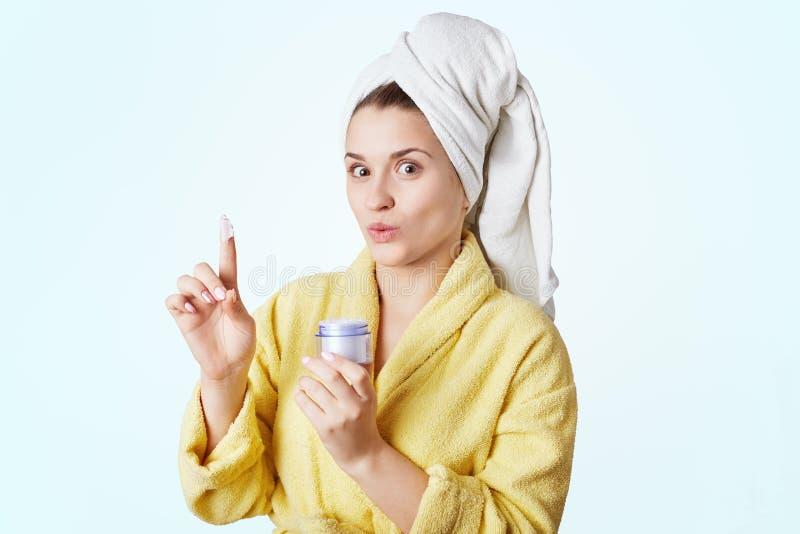 Ładna młoda kobieta iść robić masce na twarzy po brać prysznic, chwyt butelka z śmietanką w ręce, demonstares ja na palcu, dresy obrazy stock