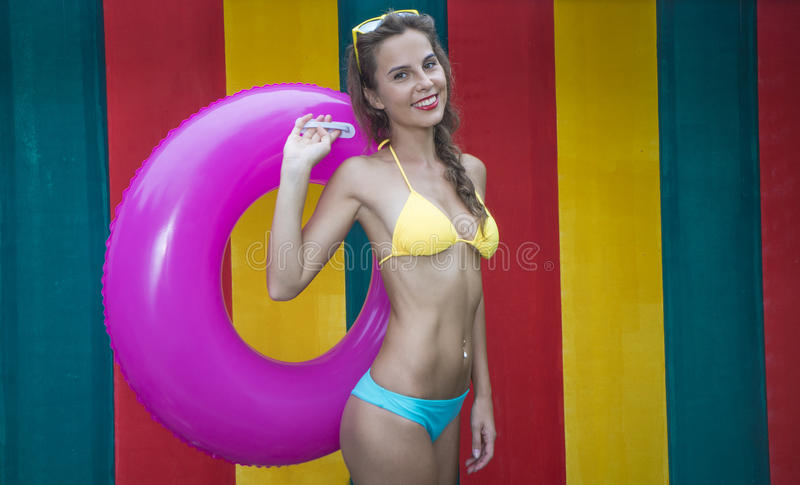Ładna młoda kobieta jest ubranym bikini mienia menchii nadmuchiwanego pierścionek na kolorowej ścianie obrazy royalty free