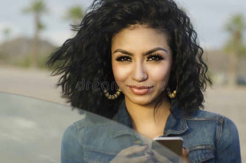 Ładna młoda kobieta obok jej samochodowej robi rozmowy telefonicza zdjęcia stock