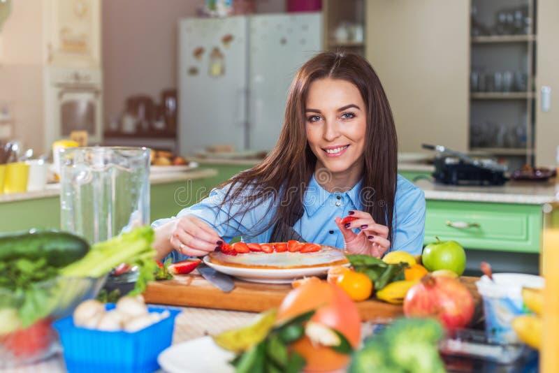Ładna młoda kobieta ono uśmiecha się przy kamerą podczas gdy dekorujący tort z pokrojonym truskawkowym obsiadaniem w dużej kuchni obraz stock