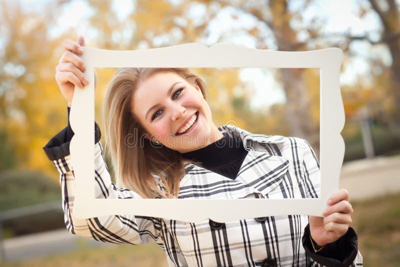 Ładna młoda kobieta ono Uśmiecha się w parku z obrazek ramą obraz stock