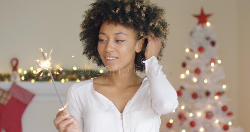 Ładna młoda kobieta pali Bożenarodzeniowego sparkler obrazy stock