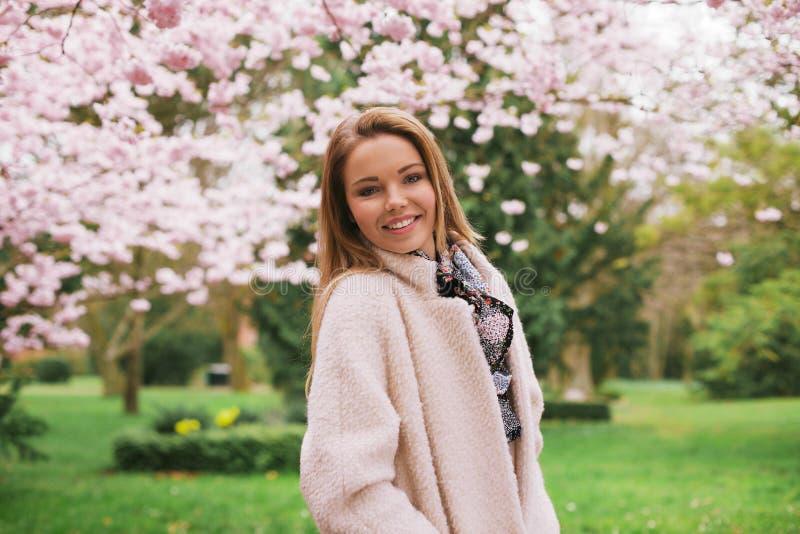 Ładna młoda kobieta pozuje przy wiosny okwitnięcia ogródem zdjęcia royalty free