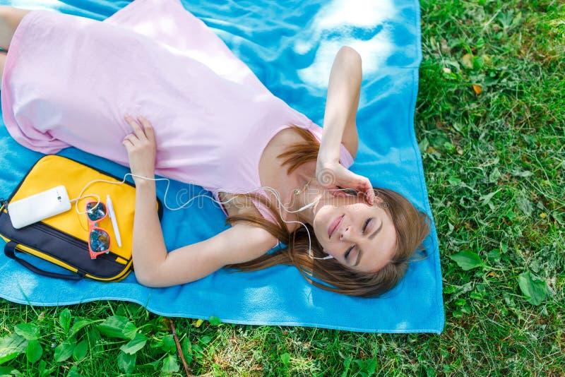 Ładna młoda kobieta relaksuje na trawie w parkowym słuchaniu muzyka na jej telefonie komórkowym zdjęcia stock