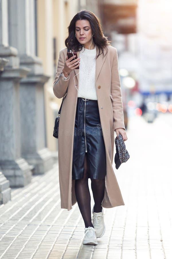 Ładna młoda kobieta słucha muzyka z jej telefonem komórkowym podczas gdy chodzący w ulicie fotografia stock