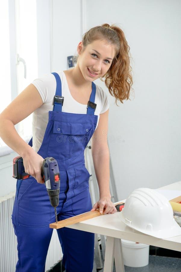 Ładna młoda kobieta trzyma cordless świder obrazy stock